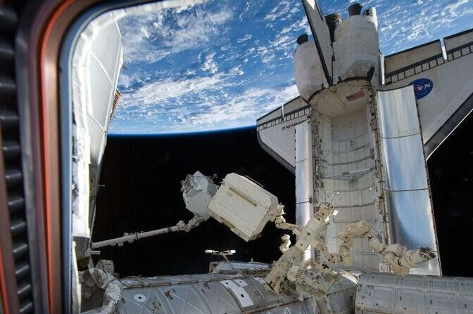 The AMS is transferred from Endeavour's payload bay to the ISS
