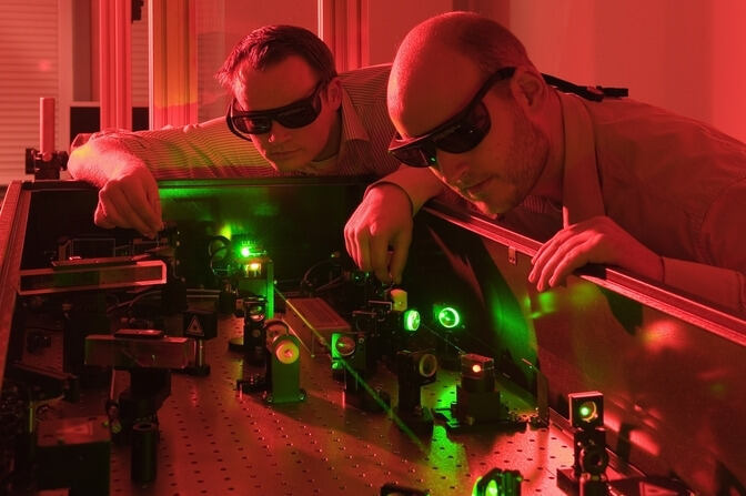 Researchers working with a laser